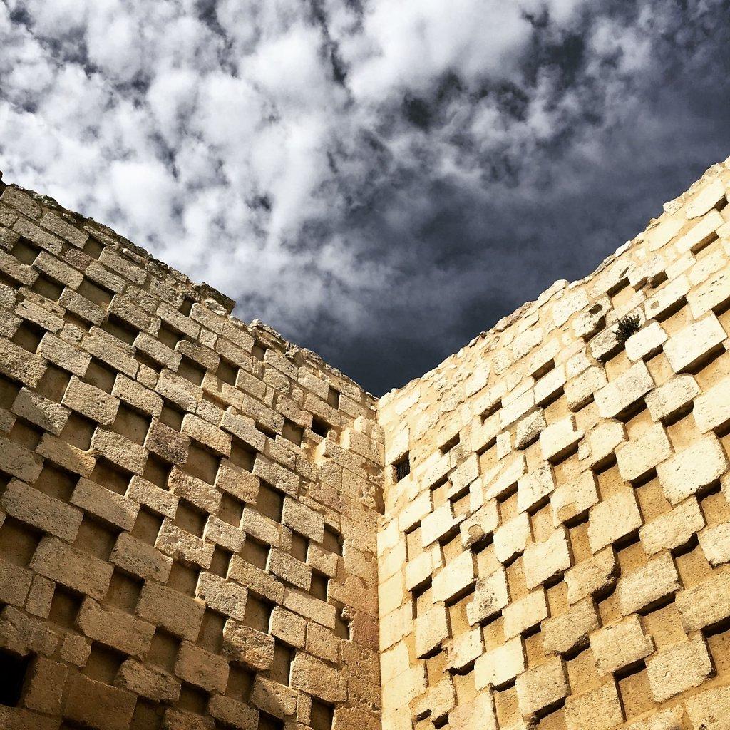 The deep blue sky and the stony wall